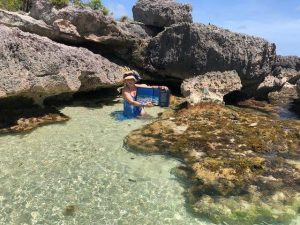 "Mrs Martha Watkins Gilkes and her signed copy in Martha's ""secret mermaid cave"". Antigua/Barbuda."