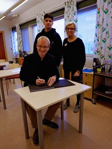 Rico Besserdich signing a copy of his book for the library of Rinkeby school, Stockholm.